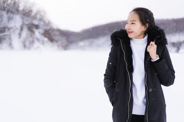 雪の冬の季節に旅行のために幸せな笑みを浮かべて美しい若いアジア女性 無料写真