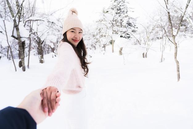 Портрет молодой красивой азиатской улыбкой счастливой женщины путешествуют и наслаждаются со снежным зимним сезоном Бесплатные Фотографии