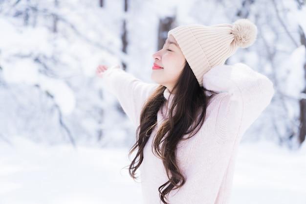 肖像画若い美しいアジアの女性は幸せな旅行を笑顔し、雪の冬の季節を楽しみ 無料写真