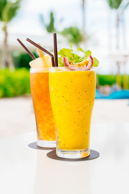 ビーチと海のガラスを飲みながらアイスカクテル 無料写真