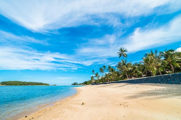 美しい熱帯のビーチの海と青い空と白い雲の上のココヤシの木と砂 無料写真