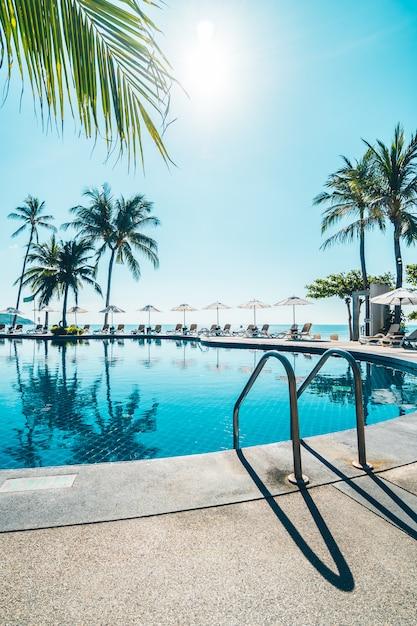 美しい熱帯のビーチと海の傘とスイミングプールの周りの椅子 無料写真