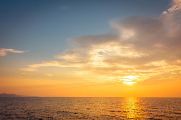 ビーチと海に沈む夕日 無料写真