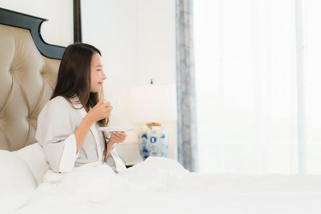 肖像画美しい若いアジア女性の幸せな笑顔と寝室のベッドの上のコーヒーカップで目を覚ます 無料写真