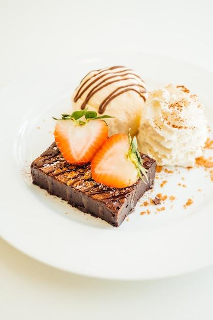 バニラアイスクリームとチョコレートブラウニーケーキの上にイチゴ 無料写真