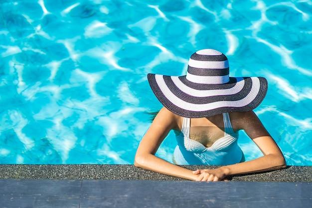 旅行や休暇のためのプールで帽子を持つ美しい若いアジア女性 無料写真