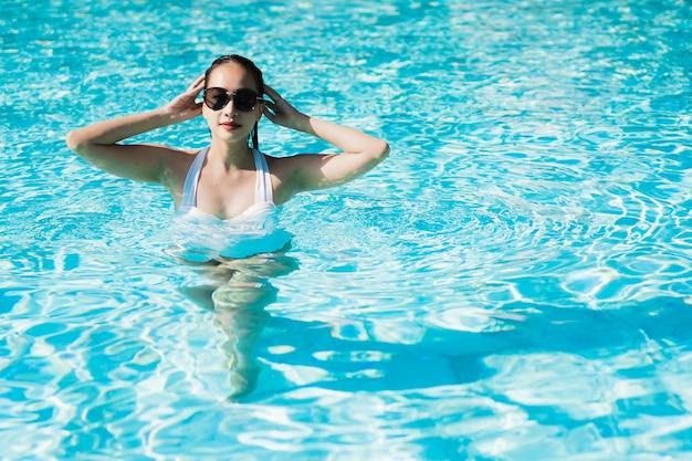 幸せな美しい若いアジア女性とリラックスした旅行や休暇のためのプールで笑顔 無料写真