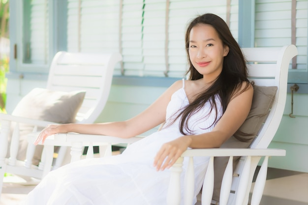 屋外パティオの周りの木製の椅子に座っている肖像画美しい若いアジア女性 無料写真