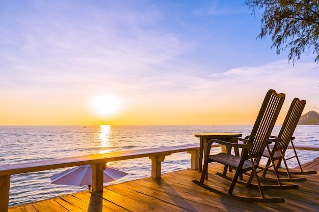 空の木の椅子と美しい熱帯のビーチと海と屋外のパティオでテーブル 無料写真