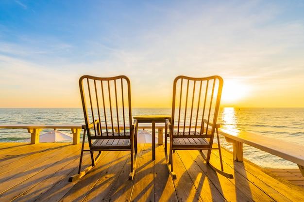Пустой деревянный стул и стол на открытом патио с красивым тропическим пляжем и морем Бесплатные Фотографии