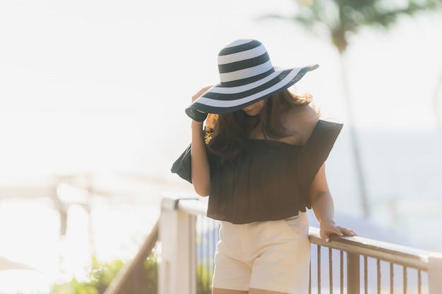 アジアの美しい若い女性の肖像画幸せとホテルリゾートニアリー海とビーチでの旅行と笑顔 無料写真