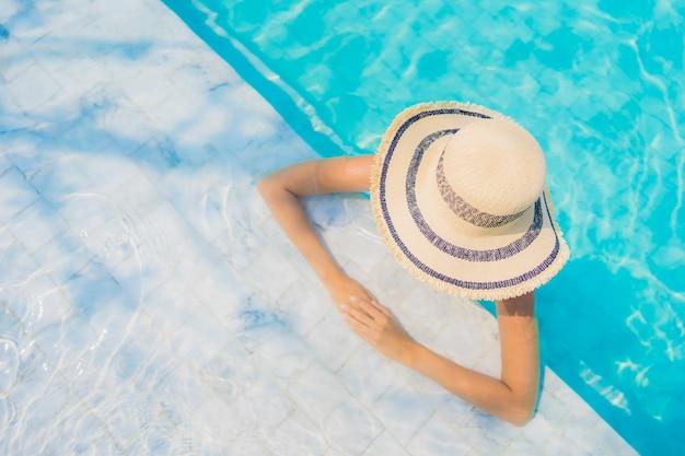 肖像画美しい若いアジア人女性の幸せな笑顔は旅行休暇のためのプールでリラックスします。 無料写真