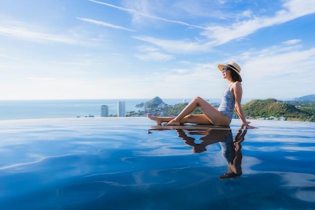 肖像画美しい若いアジア女性笑顔幸せなレジャーのためのホテルリゾートのプールの周りリラックス 無料写真