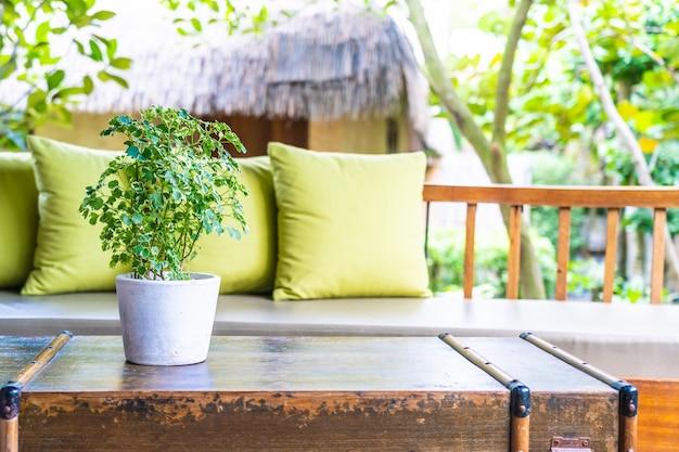 ソファの椅子に枕とテーブルデコレーションの花瓶植物 無料写真