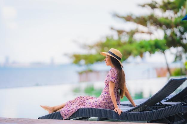 肖像画美しい若いアジア女性の幸せな笑顔は青い空にホテルリゾートニアリー海オーシャンビーチでプールでリラックスします。 無料写真