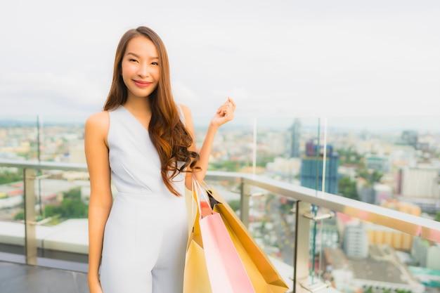 幸せな肖像画美しい若いアジア女性とデパートからの買い物袋と笑顔 無料写真