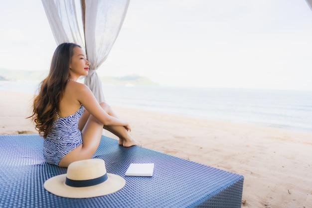 Книга чтения женщины портрета красивая молодая азиатская с счастливой улыбкой ослабляет в кресле шезлонга на океане моря пляжа для отдыха Бесплатные Фотографии