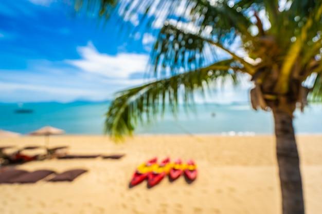 抽象的なぼかしとデフォーカス美しい熱帯のビーチの海とヤシの木と傘と青い空に椅子と海 無料写真