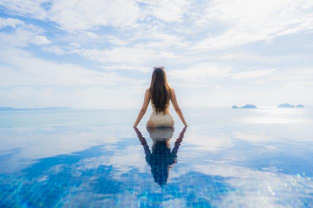 アジアの若い女性の肖像画はホテルやリゾートのプールの周り幸せな笑顔をリラックス 無料写真