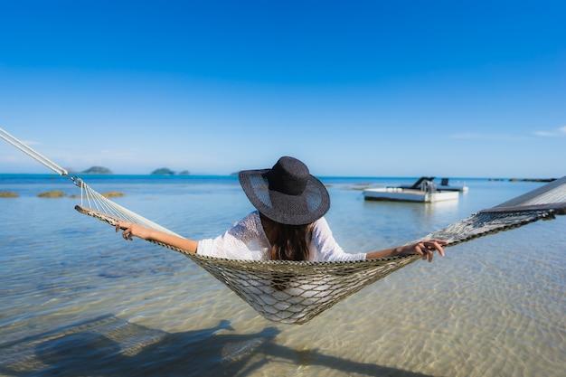 Женщина портрета красивая молодая азиатская сидя на гамаке вокруг океана пляжа моря для ослабляет Бесплатные Фотографии