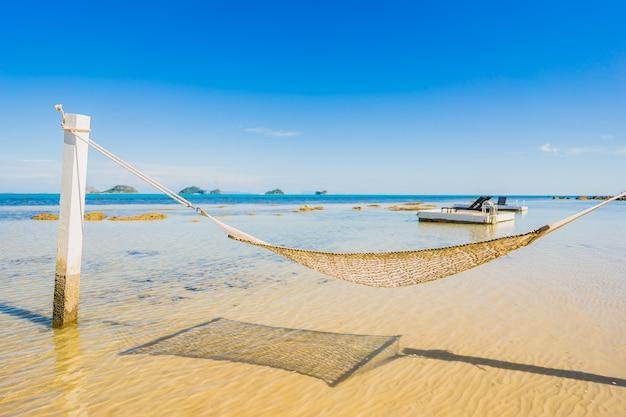 休日の休暇のための熱帯のビーチ海海の周りの美しい空のハンモック 無料写真