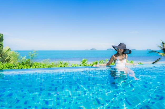 Портрет красивая молодая азиатская женщина расслабиться в роскошном открытом бассейне в отеле курорта почти пляж море океан Бесплатные Фотографии