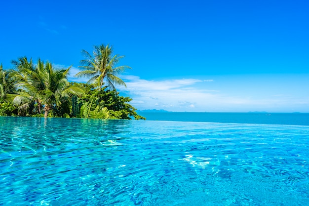 ココヤシの木と青い空に白い雲の周りの海とホテルリゾートの美しい高級屋外スイミングプール 無料写真