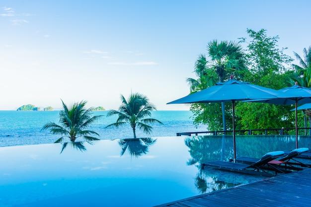 Зонтик и стул вокруг красивого роскошного открытого бассейна с видом на море и море в курортном отеле для отпуска Бесплатные Фотографии