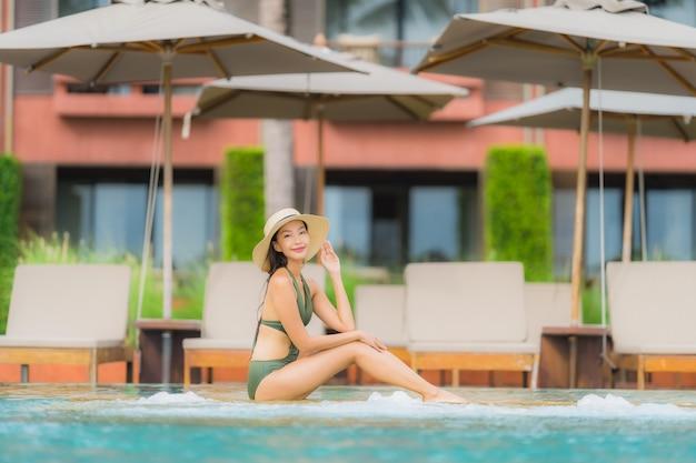 肖像画美しい若いアジア女性はホテルのリゾート地の高級屋外スイミングプールでほぼビーチ海海でリラックスします。 無料写真