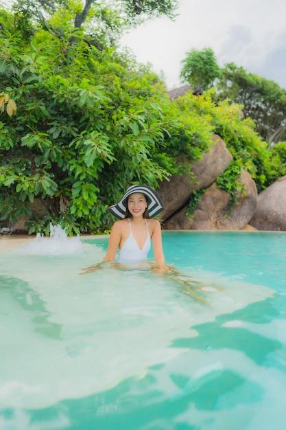 アジアの若い女性の肖像画は、海のオーシャンビューのホテルリゾートの屋外スイミングプールの周り幸せな笑顔をリラックス 無料写真