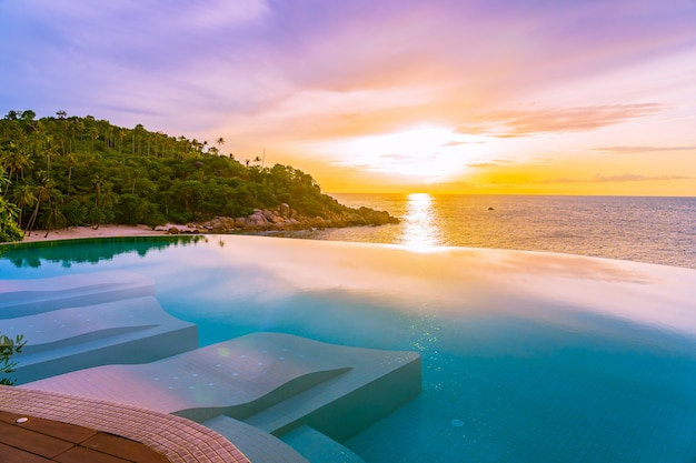 海のオーシャンビューと白い雲の青い空とホテルリゾートの美しい屋外インフィニティプール 無料写真