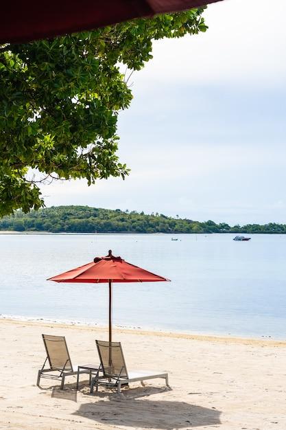 白い雲青い空の上の周りの傘の椅子とラウンジデッキの美しい屋外熱帯ビーチ海 無料写真