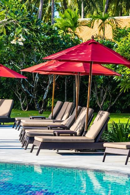 休日休暇旅行のためのホテルリゾートの屋外スイミングプールの周りの美しい傘と椅子 無料写真