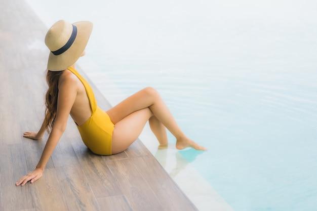 Улыбка азиатской красивой молодой женщины портрета счастливая ослабляет вокруг открытого бассейна в каникулах праздника Бесплатные Фотографии