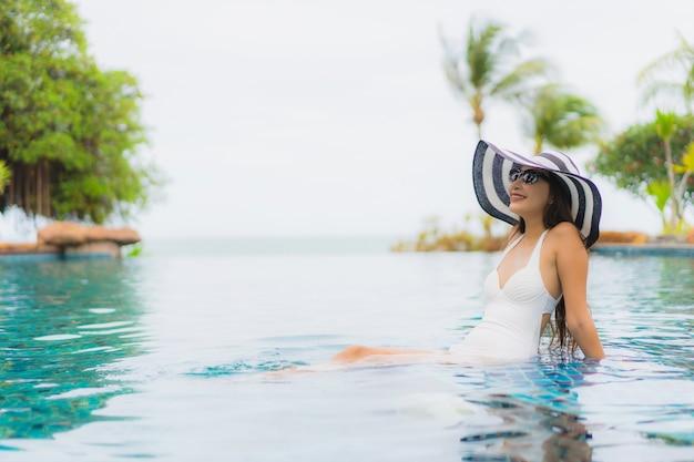 肖像画美しい若いアジア女性笑顔幸せなホテルリゾートのスイミングプールの周りでリラックス 無料写真