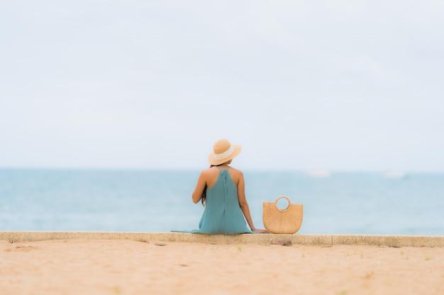 Улыбка красивых азиатских женщин портрета счастливая ослабляет вокруг океана моря пляжа Бесплатные Фотографии