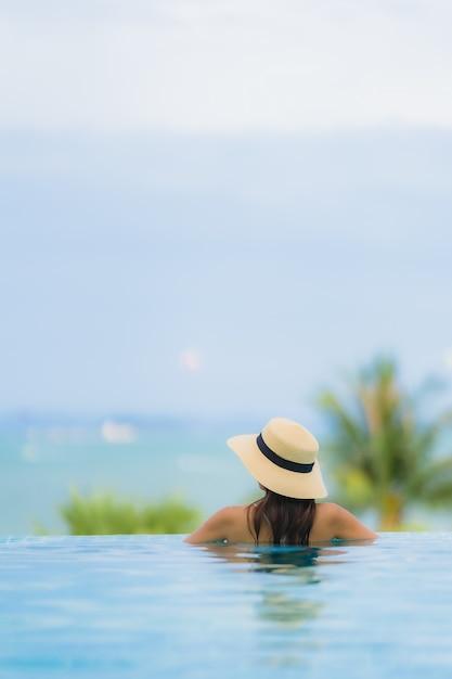 Улыбка молодой азиатской женщины портрета счастливая ослабляет вокруг бассейна в курорте гостиницы Бесплатные Фотографии