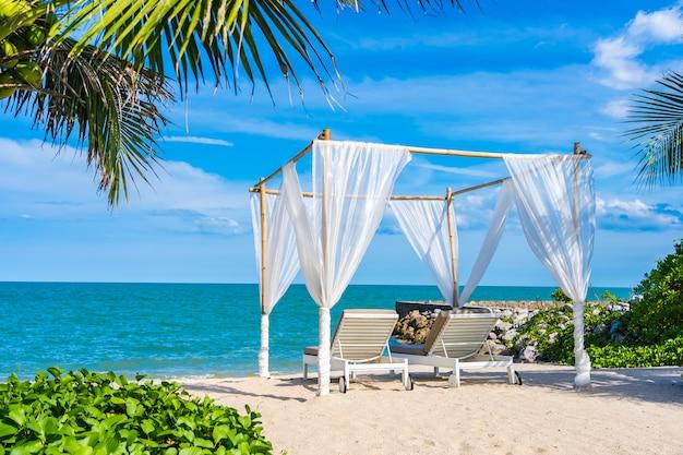 旅行のための青い空とビーチ海海の周りの美しい傘と椅子 無料写真