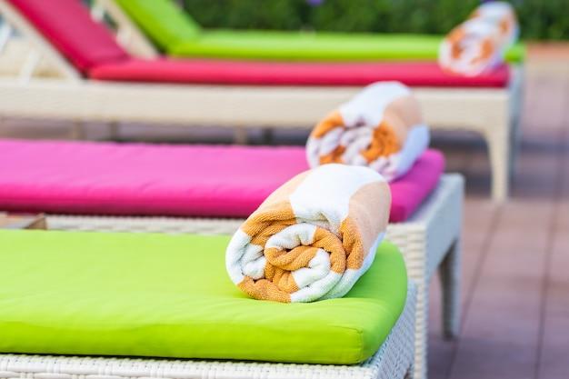 ホテルリゾートのプールの周りのベッドの上のタオル 無料写真