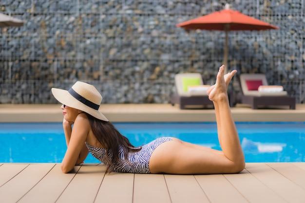 Женщина красивого портрета азиатская ослабляет счастливую улыбку вокруг открытого бассейна Бесплатные Фотографии