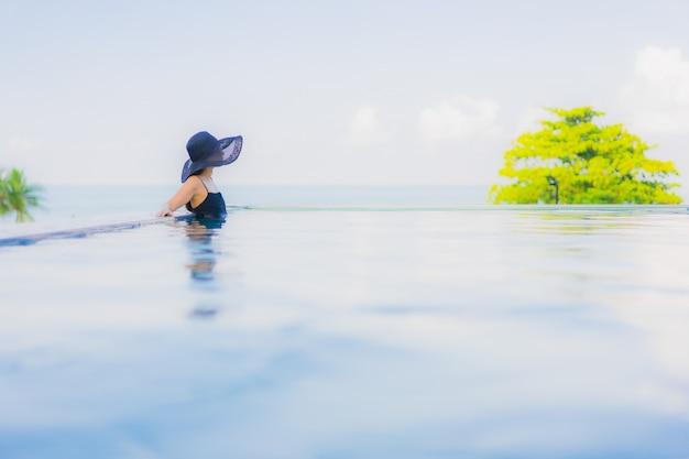 Улыбка красивых молодых азиатских женщин портрета счастливая ослабляет открытый бассейн в гостинице Бесплатные Фотографии