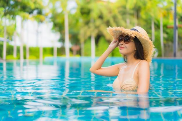 肖像画美しい若いアジア女性の幸せな笑顔はリゾートの屋外スイミングプールをリラックスします。 無料写真