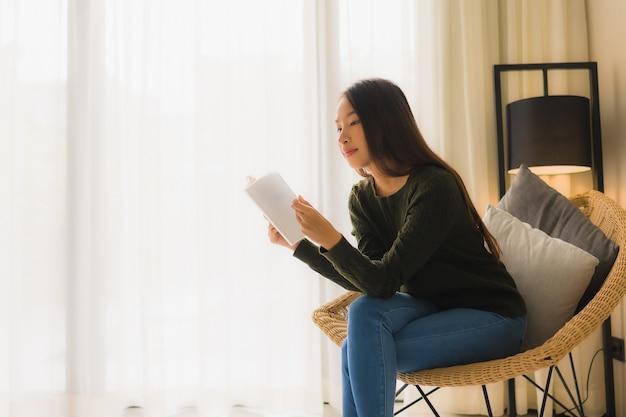 Книга чтения красивых молодых азиатских женщин и сидеть на стуле софы Бесплатные Фотографии