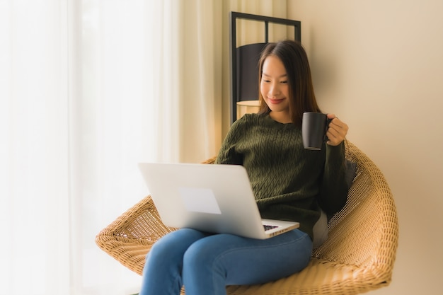 Женщины портрета красивые молодые азиатские используя компьютер или компьтер-книжку для работы и сидеть на стуле софы Бесплатные Фотографии