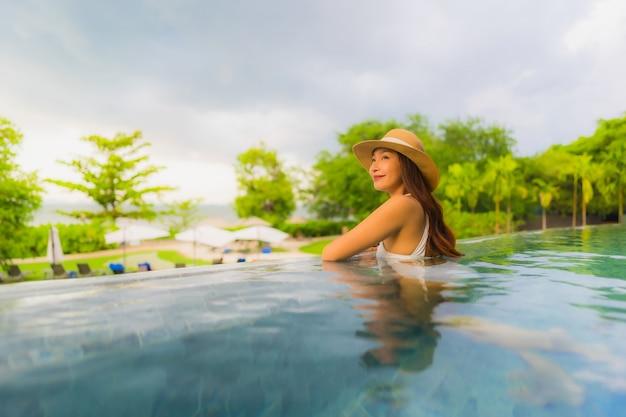 Улыбка красивых молодых азиатских женщин портрета счастливая ослабляет вокруг открытого бассейна в гостинице Бесплатные Фотографии