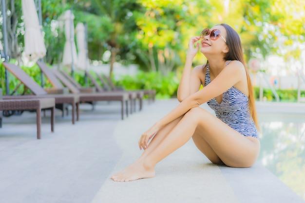 美しい若いアジア女性の幸せな笑顔は、ホテルリゾートの屋外スイミングプールの周りでリラックスします。 無料写真