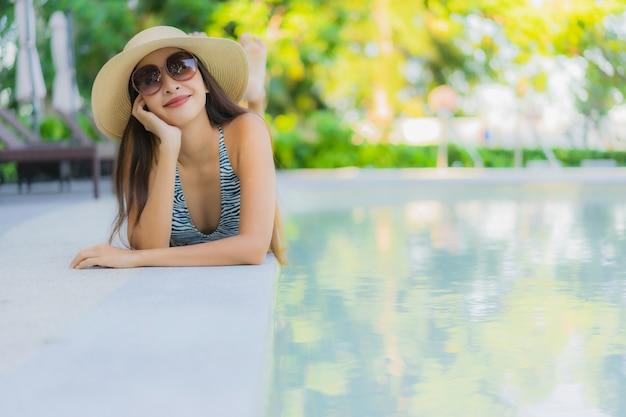 Улыбка красивых молодых азиатских женщин счастливая ослабляет вокруг открытого бассейна в курорте гостиницы Бесплатные Фотографии