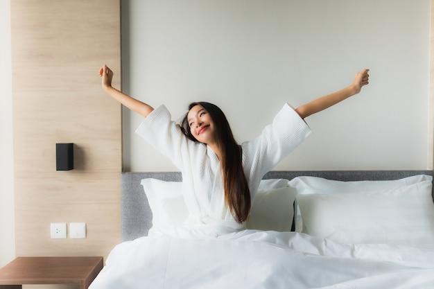 肖像画美しい若いアジア女性の幸せな笑顔はベッドでリラックス 無料写真
