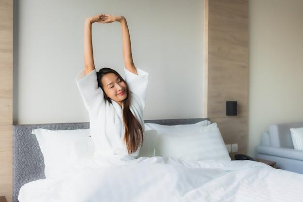 Улыбка красивых молодых азиатских женщин портрета счастливая ослабляет на кровати Бесплатные Фотографии