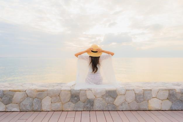 Улыбка красивых молодых азиатских женщин портрета счастливая ослабляет вокруг океана пляжа моря Бесплатные Фотографии